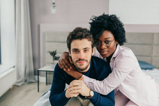 Faithful, affectionate african woman is sitting behind and hugging tenderly her handsome husband, they looking at camera while sit on the bed in spacious room.