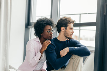 Interracial married couple embrace affectionately at home interior, sitting near large window, feel support and emotional resource from each other, have close relationship.