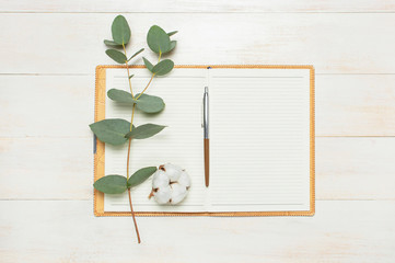 Open notebook with blank pages, pen, eucalyptus twig and cotton flowers on white wooden background top view flat lay. Fashion female blogger working desk. Cotton flowers. Lifestyle gentle background