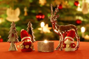 Weihnachtliche Tischdekoration vor Weihnachtsbaum