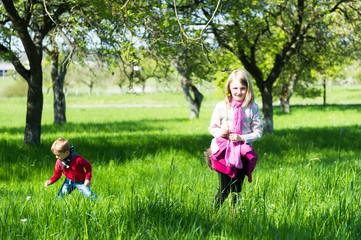 Deux enfants jouent dans un verger au printemps