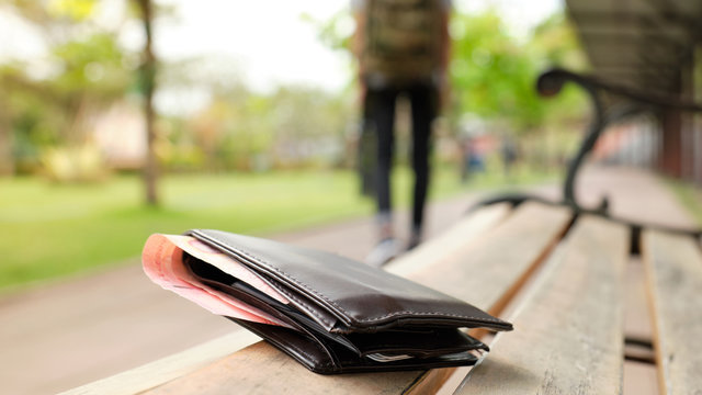 Leather purse with a money lying on the park bench while tourists are walking away. - image