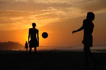 Siluetas de amigos en contraluz divirtiéndose en la puesta de sol.