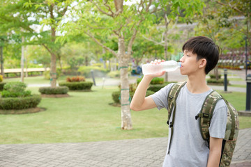 Asian traveler with backpack is drinking water Because the weather is hot and tired. - image