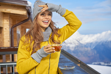 Woman drinking tea in the rustic wooden outdoor cafe mountain summit. Lifestyle adventure concept.