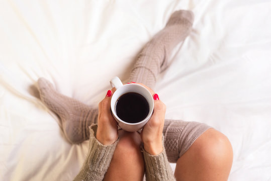 Woman sitting in bed drinking a cup of coffee .