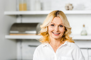 smiling attractive middle aged woman looking at camera in kitchen