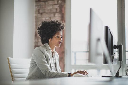 Businesswoman working on desktop computer in office