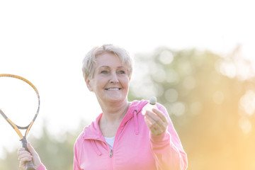 Sporty senior woman playing badminton with tennis racket in park