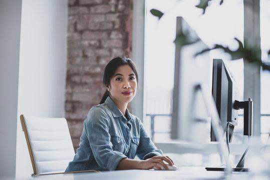 Portrait of businesswoman working on desktop computer in office