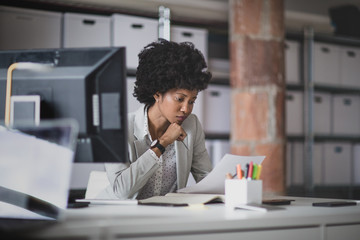 Female african american business executive working in an office looking at paperwork