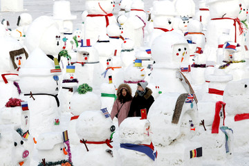 A couple walk between snowmen on Songhua River that displays 2019 snowmen as a part of annual ice festival, in the northern city of Harbin, Heilongjiang province
