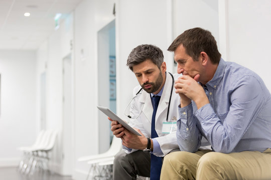 Mid adult doctor explaining serious patient over digital tablet at hospital