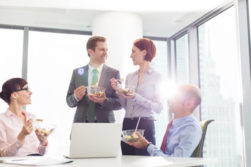 Smiling business colleagues eating lunch in boardroom during meeting at office
