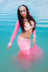 Young beautiful woman posing in pink sexy costume in blue water