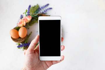 Female hand with a phone takes pictures of an Easter wreath with bright spring flowers, a nest with Easter eggs