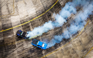 Aerial view from drone. Sport car wheel battle drifting. Blurred of image diffusion race battle drift car with lots of smoke from burning tires on speed track.