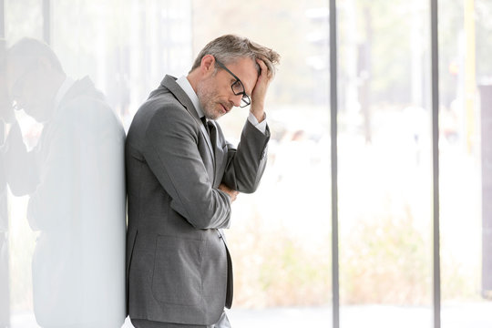 Thoughtful mature businessman scratching head while standing at office