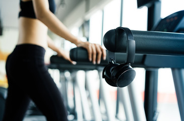 Closeup headphone Exercise treadmill cardio running workout at fitness gym of woman taking weight loss with machine aerobic for slim and firm healthy in the morning.