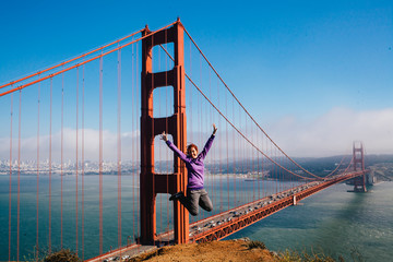 Woman jumping in front of the Golden Gate