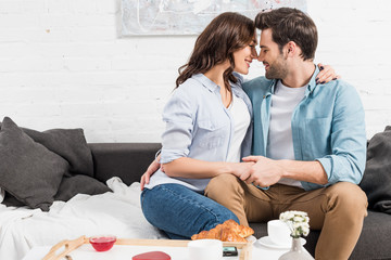 couple sitting on couch and tenderly embracing while having breakfast at home