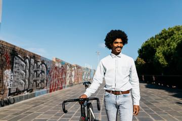Mid adult man pushing his bicycle next to a graffiti wall