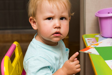 Girl baby with an angry look sitting at the children's table. On the table are toys and educational game. Copy space.