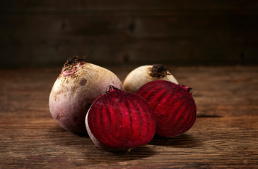 Whole and sliced beetroot on dark wood, copy space