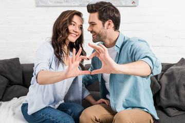 happy couple in casual clothes showing heart sign with hands at home