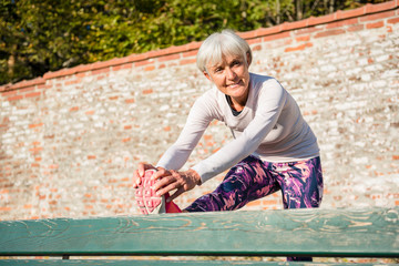 Smiling senior woman stretching on a bench