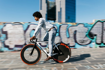Mid adult man riding bicycle in front of a graffiti wall