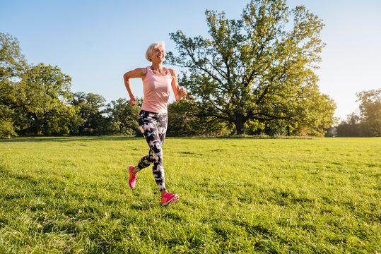 Senior woman running on rural meadow