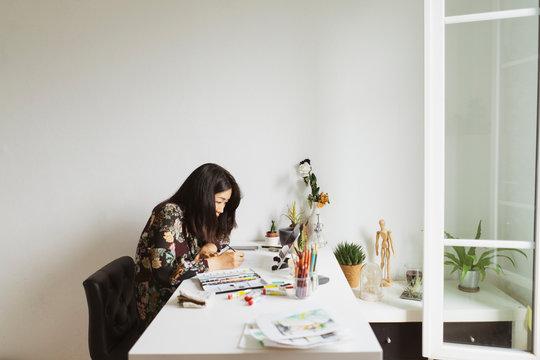Illustrator at work desk in an atelier using digital tablet for painting