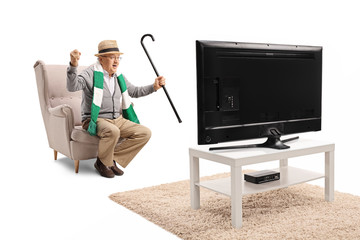 Senior male sports fan with a cane and a scarf sitting in an armchair watching a game on tv and cheering