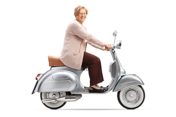 Senior woman riding a vintage scooter and smiling at the camera