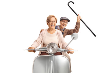 Cheerful senior couple riding a vintage scooter and holding a cane up