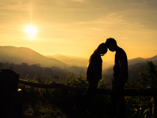 Silhouette of happy young couple in love looking view sunset on the mountain. Romantic couple in love kissing.