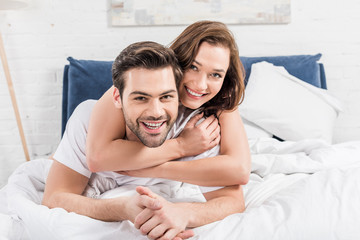 happy couple looking at camera and cuddling in bed at home