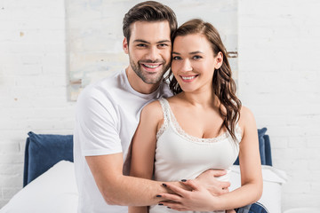beautiful smiling couple embracing and looking at camera in bedroom