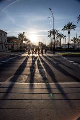 Menschen laufen in die Sonne, lange Schatten