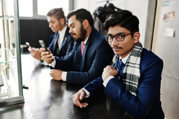 Group of three indian businessman in suits sitting on cafe.