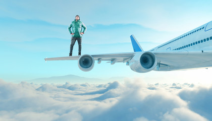 The young man stands on the wing of a plane