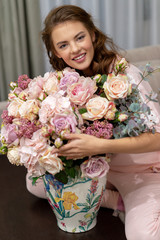 Attractive woman with bouquet of hundreds of flowers is spending time at home.