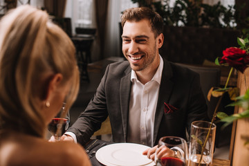 handsome man laughing in restaurant while looking at woman