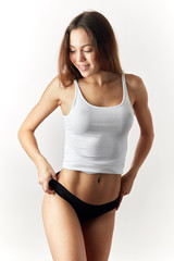 happy awesome brown-haired girl is going to take eoff her clothes. isolated white background. studio shot