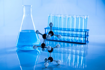 Laboratory beakers, microscope, blue background