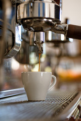 Always taste great. Small cup to serve hot coffee drink. Brewing coffee with espresso machine. Espresso being brewed in coffeehouse or cafe. Coffee cup. Making espresso with portafilter