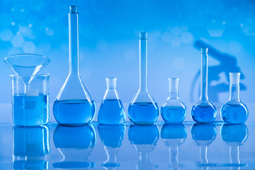 Laboratory beakers, microscope, blue background