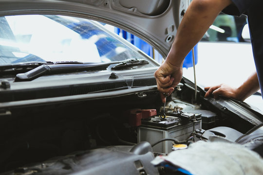mechanic opening closing checking car battery in automobile repair service