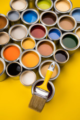 Paint can with a paintbrush, yellow background